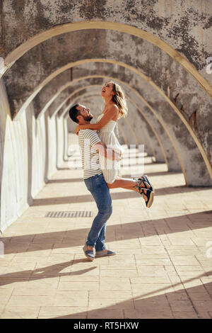 Spain, Andalusia, Malaga, happy man lifting up girlfriend under an archway in the city - Stock Photo