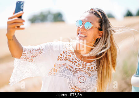 Portrait of blond young woman wearing mirrored sunglasses taking selfie with smartphone - Stock Photo