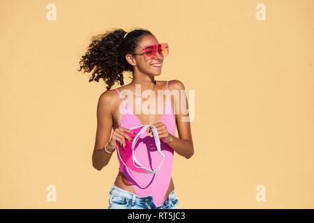 Portrait of teenage girl wearing sunglasses, orange wall - Stock Photo