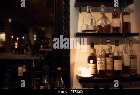 A large mirror and several bottles of alcohol on the shelves behind a bar. - Stock Photo