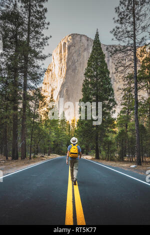 USA, California, Yosemite National Park, man walking on road with El Capitan in background - Stock Photo