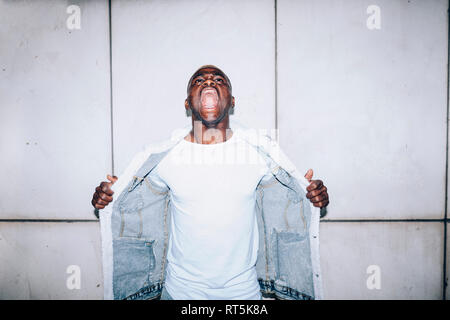 Angry young man standing at a wall shouting - Stock Photo