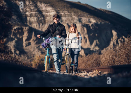 Boy and girl walking on the train track with bicycles - Stock Photo