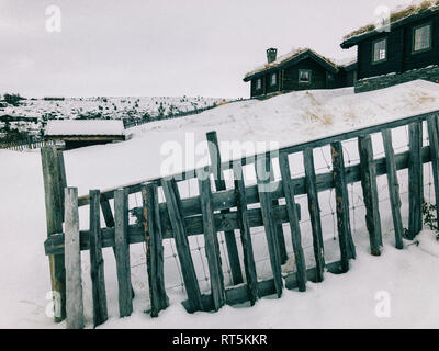 Norway, Rondane, Traditional Cabins in Norwegian Mountain Resort on Overcast Winter Day - Stock Photo