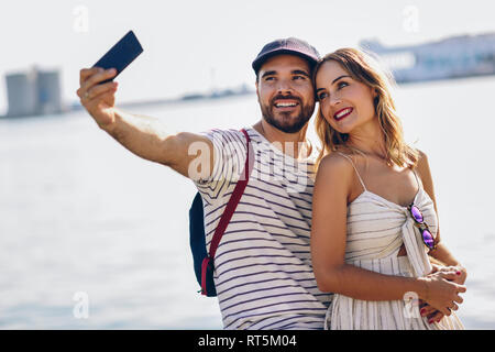 Spain, Andalusia, Malaga, happy tourist couple taking selfie with smartphone at the coast - Stock Photo