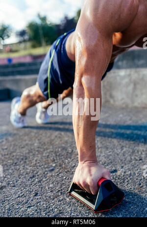Close-up of barechested muscular man doing push-ups outdoors - Stock Photo