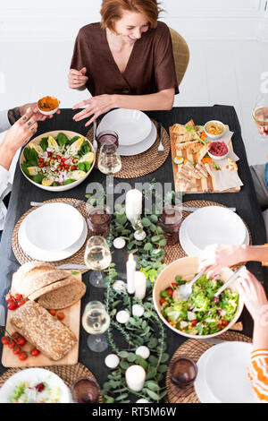 Friends sitting at laid table, enjoying their dinner party, view from above - Stock Photo