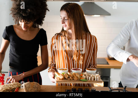 freinds preparing dinner party in the kitchen - Stock Photo