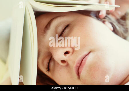 Portrait of young woman sleeping with book on head, close-up - Stock Photo