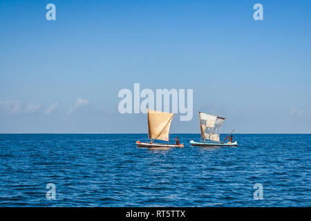 Anakao, Madagascar, october 21, 2016: Two traditional outrigger canoes sailing off Anakao in southern Madagascar - Stock Photo