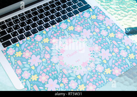 A thank you card sitting on a computer keyboard, online thank you. - Stock Photo