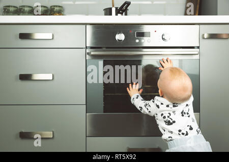 Little child playing with electric stove in the kitchen. Baby safety in kitchen - Stock Photo