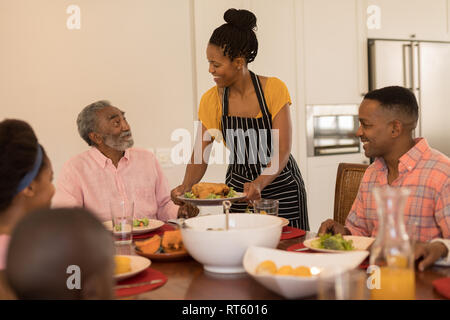 Woman serving food to her family on dining table - Stock Photo