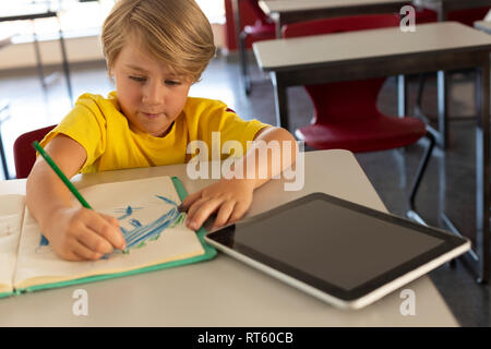 Boy drawing sketch on notebook at desk in a classroom - Stock Photo