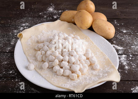 Goodies potato in the plate raw on the wooden board - Stock Photo