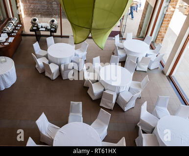 A top-down view of an empty restaurant with chairs and tables arranged in a circular pattern, to host a buffet. Hyderabad, Telangana, India. - Stock Photo