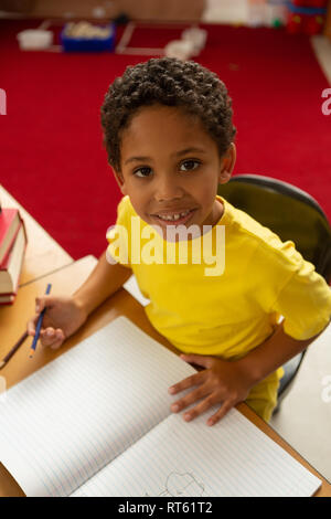 Schoolboy looking at camera while drawing in notebook at desk in a classroom - Stock Photo