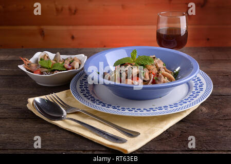 Plate of spaghetti with clams fish and shellfish on wooden table - Stock Photo