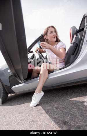 modern young woman sitting in a luxury car - Stock Photo