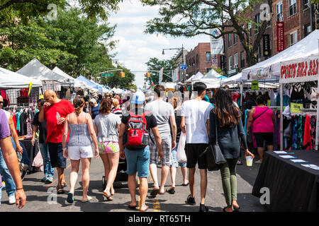 Astoria, New York, USA - 29 July 2018: Many people walking down the street looking to purchase goods from the vendors at a Queens street fair. - Stock Photo