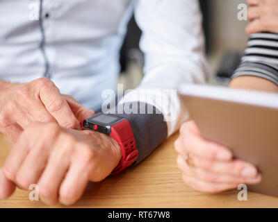 Close-up of businessman and businesswoman with smartwatch and tablet in office