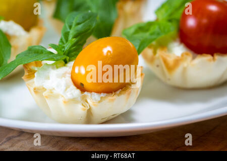 delicious puff pastry cups filled and baked with goat cheese topped with fresh basil and cherry tomato - Stock Photo
