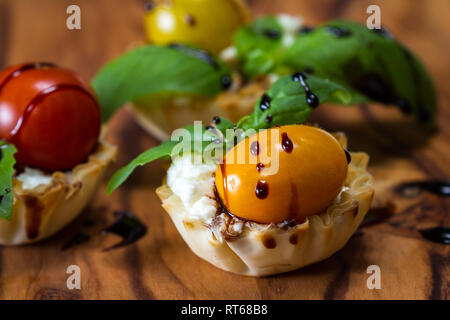 delicious puff pastry cups filled and baked with goat cheese topped with fresh basil and tomato with a balsamic drizzle - Stock Photo