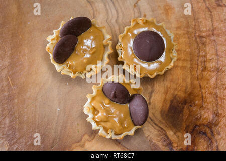 baked phyllo dough cups filled with peanut butter topped with dark chocolate wafers - Stock Photo