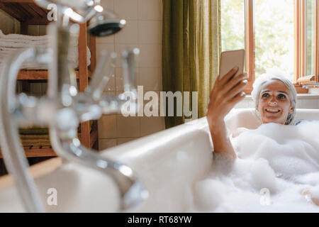 Portrait of happy woman in bathtub taking selfie with cell phone - Stock Photo