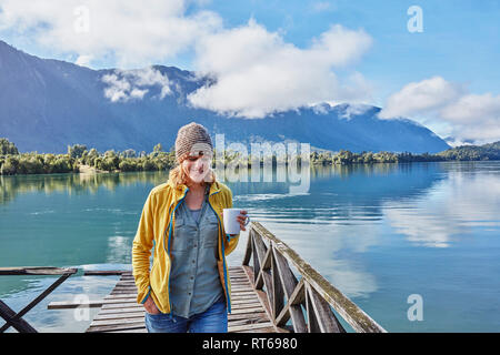 Chile, Chaiten, Lago Rosselot, woman walking on jetty holding mug