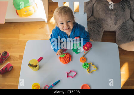 Portrait of smiling baby girl playing with modeling clay in children's room - Stock Photo
