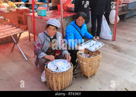 Shaxi, China - February 22, 2019: Chinese women selling local cheese in the Friday market in Shaxi old town - Stock Photo