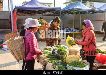 Shaxi, China - February 22, 2019: Chinese women selling local vegetables in the Friday market in Shaxi old town - Stock Photo