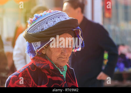 Shaxi, China - February 22, 2019: Portrait of an old Chinese woman in the Friday market in Shaxi old town - Stock Photo