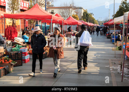 Shaxi, China - February 22, 2019: Chinese women in the Friday market in Shaxi old town - Stock Photo