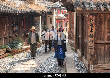 Shaxi, China - February 22, 2019: Horses riding in the center of Shaxi old town at dusk - Stock Photo
