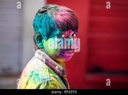 Udaipur, India - March 6, 2015: Portrait of Indian boy with painted face celebrating the colorful festival of Holi on the street. - Stock Photo