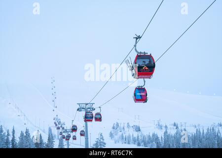 Ylläs ski resort and gondola lift with people in them in Kolari and Äkäslompolo, Finland - Stock Photo