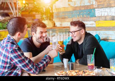 Three young men enjoy drinking beer at trendy pub - Stock Photo