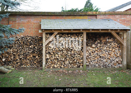 Log store filled with cut logs for firewood in a garden - Stock Photo