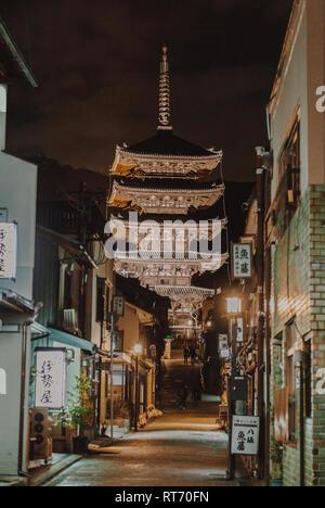 Beautiful pagoda temple in Higashiyama at night with street lights and tourists walking. - Stock Photo
