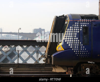 Front of Scotrail class 380 Desiro electric multiple unit train and view down River Clyde from rail bridge outside Glasgow Central station 25 Feb 2019 - Stock Photo
