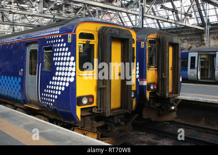 Two class 156 super sprinter diesel multiple units in different Scotrail liveries waiting at platforms in Glasgow Central railway station 25 Feb 2019. - Stock Photo