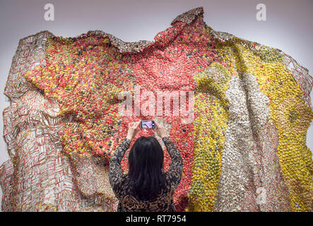 October Gallery, London, UK. 28 February, 2019. El Anatsui: Material Wonder features the Ghanaian sculptors distinctive large and intricate metal wall sculptures made from assemblages of Aluminium bottle tops from alcohol recycling stations sewn together with Copper wire. Image: Gallery staff with Rehearsal, 2015. Credit: Malcolm Park/Alamy Live News. - Stock Photo