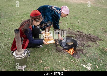 Kazakh women in traditional attire frying baursaki in a field over a wood fire, Saty, Kazakhstan - Stock Photo