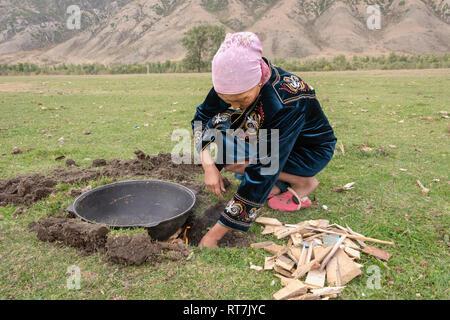 Woman lighting a fire under the wok to fry baursaki (Kazak fried dough), Saty, Kazakhstan - Stock Photo