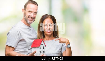 Middle age hispanic casual couple buying new house over isolated background with surprise face pointing finger to himself - Stock Photo