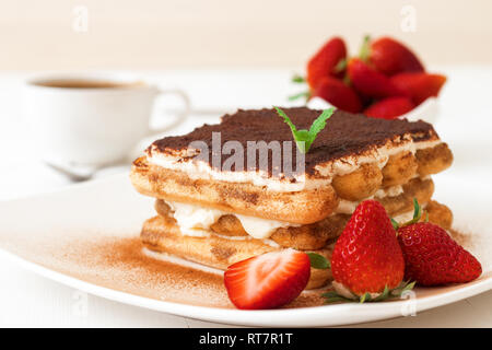Tiramisu, homemade sweet cheesecake style dessert, on white plate embellished with fresh mint and a few real strawberries, cup of coffee, bowl with st - Stock Photo