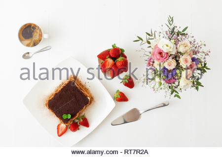 Tiramisu, homemade sweet no bake cheesecake style dessert, on white plate embellished with fresh mint and a few real strawberries, cup of coffee, bowl - Stock Photo