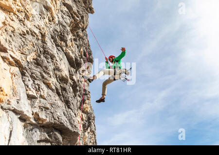 Italy, Cortina d'Ampezzo, man abseiling in the Dolomites mountains - Stock Photo